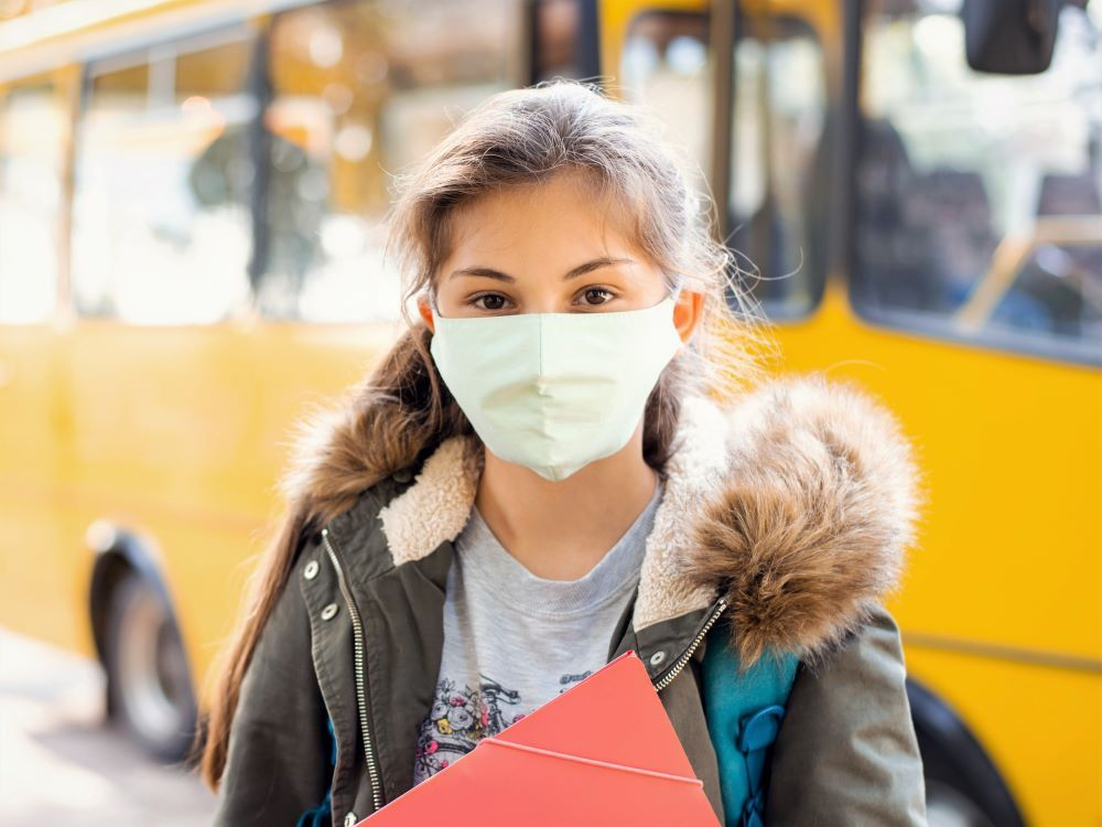 student with mask standing in front of bus
