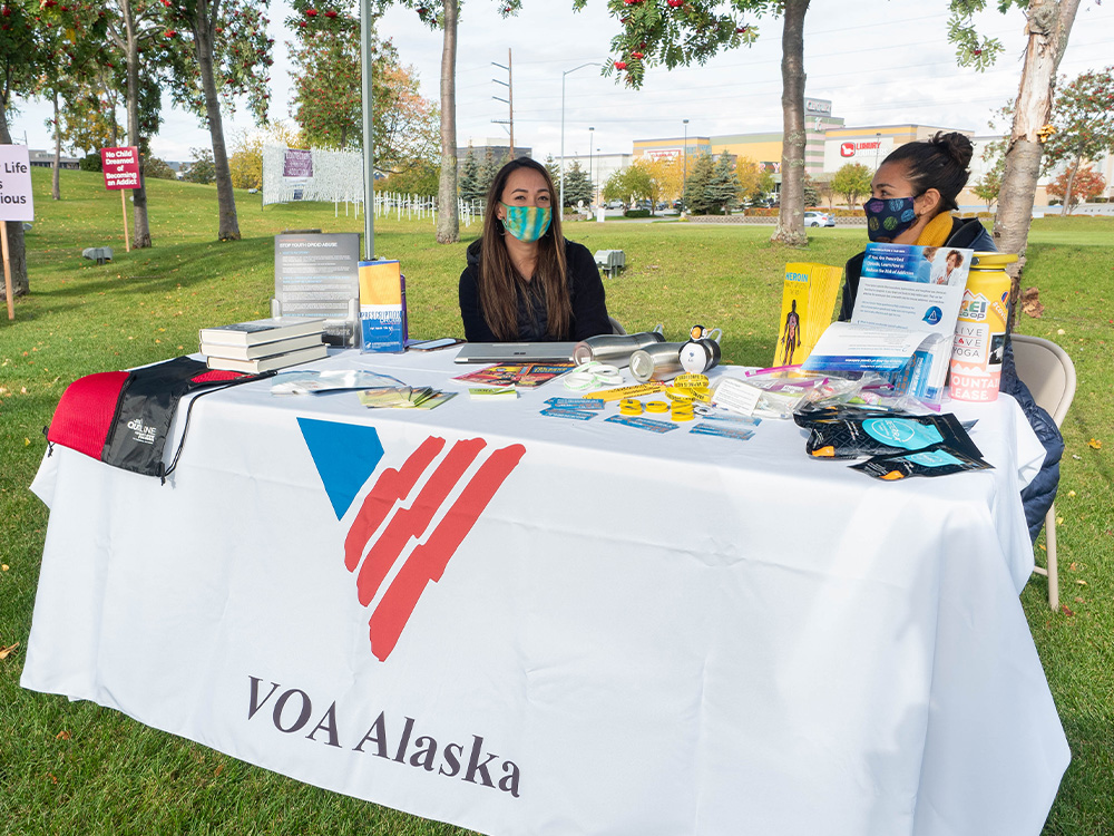 Two VOA Alaska staff at a table during an outdoor event