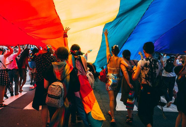 People walking under a large Pride flag
