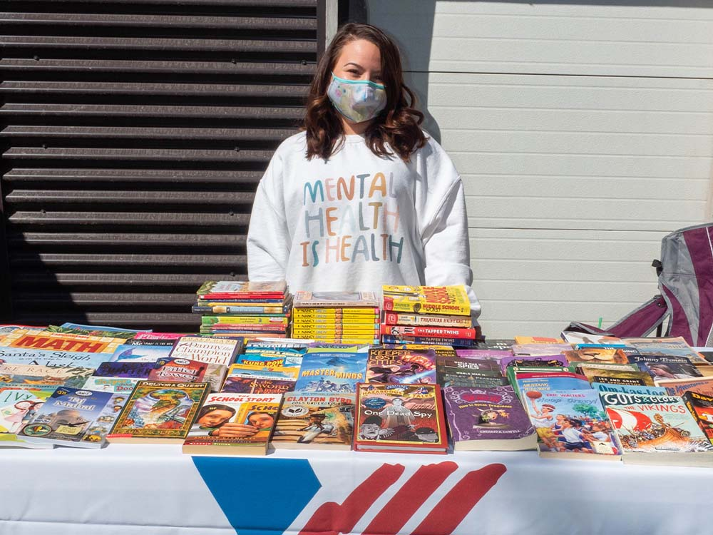 Kinship staff member standing behind a table of books