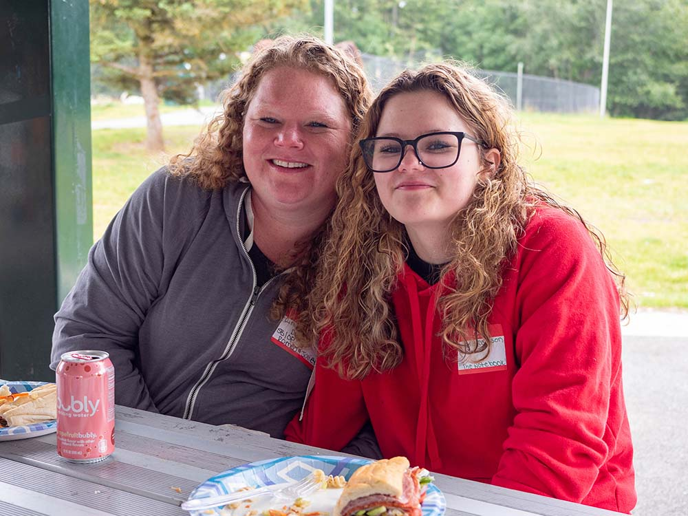 Mother and daughter sitting together at a picnic table