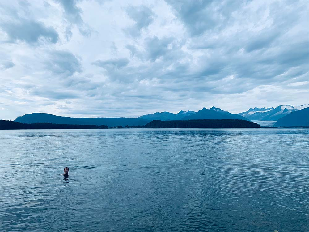Person swimming in ocean surrounded by mountains.