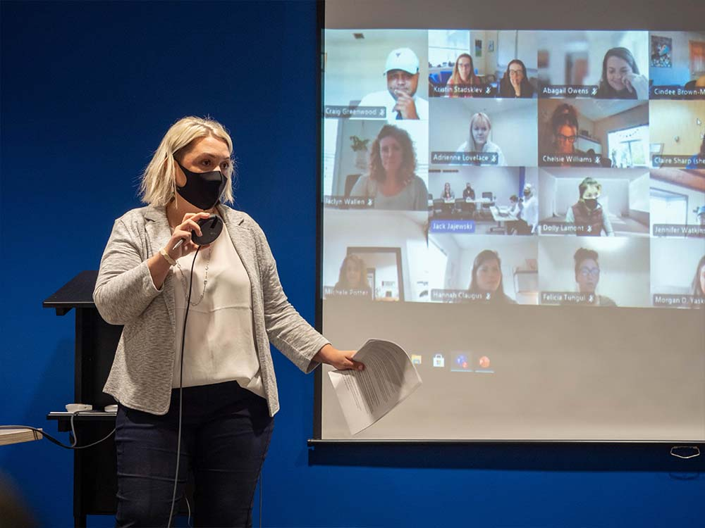 Woman speaking to unseen audience with a videoconference grid projected behind her